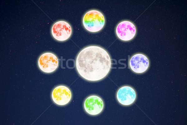 Rainbow colored moons around the full moon on starry sky Stock photo © TasiPas