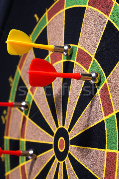 Closeup of a dartboard with yellow and red magnetic darts Stock photo © Tatik22