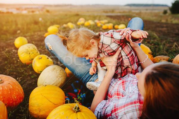 mother and daughter lie between pumpkins Stock photo © tekso