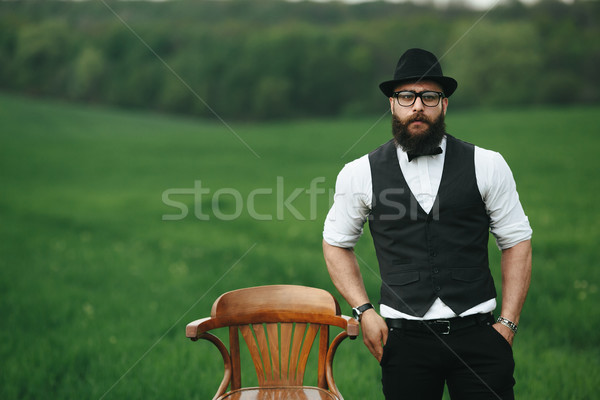 man with a beard, thinking in the field near chair Stock photo © tekso