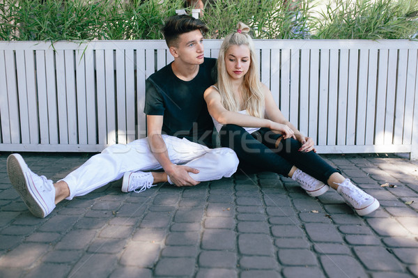 Stock photo: man and woman sitting on the ground