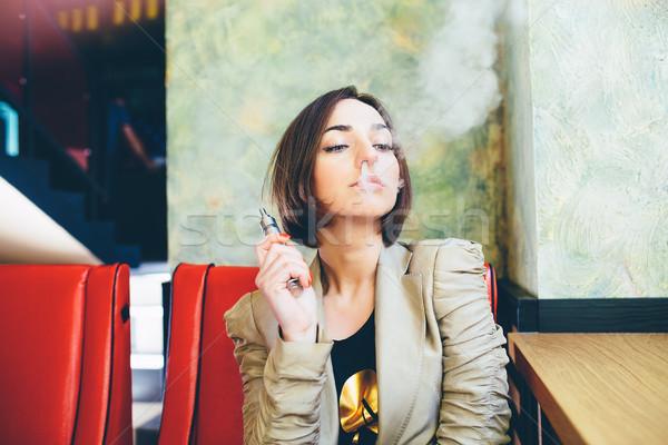 girl sits and smokes electronic cigarette Stock photo © tekso