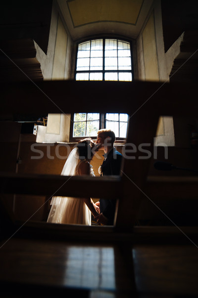 Stock photo: bride and groom on the background of a window.