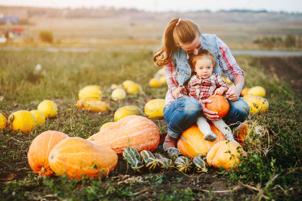 Mother and daughter sitting on pumpkins Stock photo © tekso