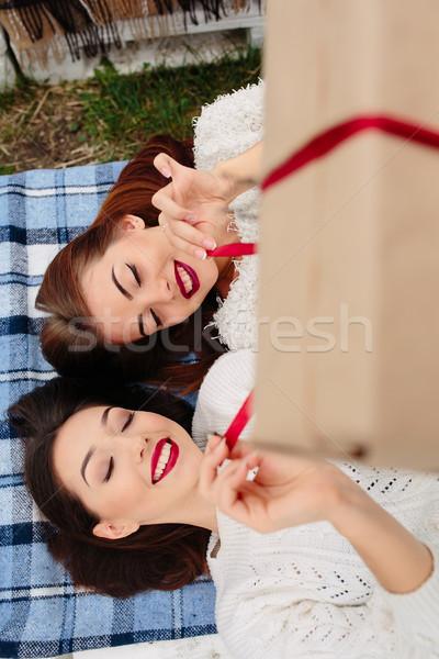 Meisjes liggen geschenk twee mooie bank Stockfoto © tekso