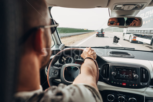 The man in the car traveling on the road Stock photo © tekso