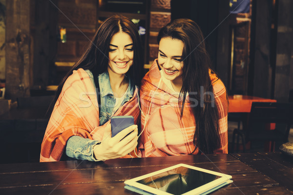 Two girl sitting listening to music with Stock photo © tekso