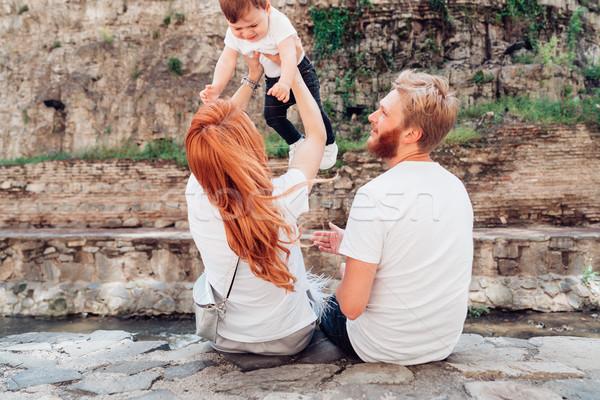 Familie zitten rivier bank rock muur Stockfoto © tekso