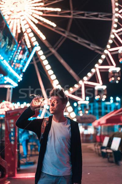 Fickó vidámpark pózol kamera fény éjszaka Stock fotó © tekso