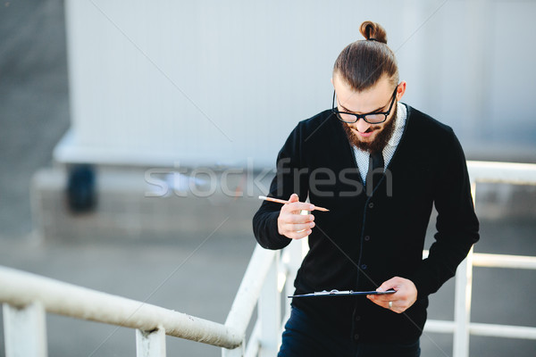 businessman stands with documents in hand  Stock photo © tekso