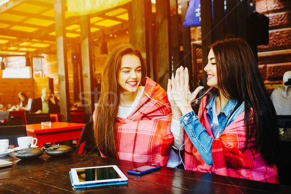 Two young and beautiful girls having fun in cafe Stock photo © tekso