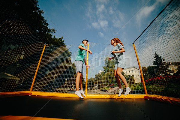 Couple jumping on trampoline in the park Stock photo © tekso