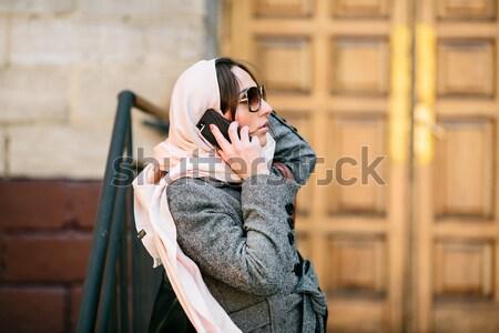 Lány kabát utca gyönyörű lány telefon instagram Stock fotó © tekso