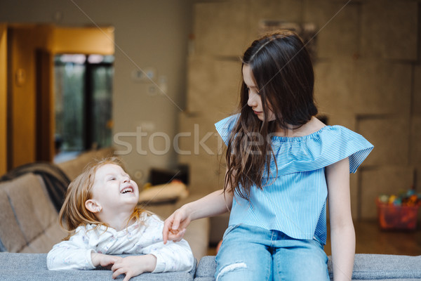 Elder and younger daughter on the big couch Stock photo © tekso