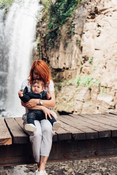 Mom and little son are sitting on the bridge Stock photo © tekso