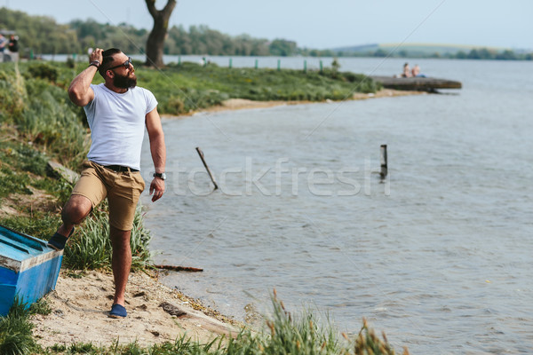 American Bearded Man using phone near the river Stock photo © tekso