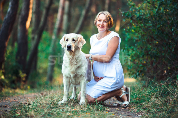 Beautiful pregnant woman and her dog Stock photo © tekso
