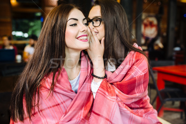 Two young and beautiful girls share secrets Stock photo © tekso