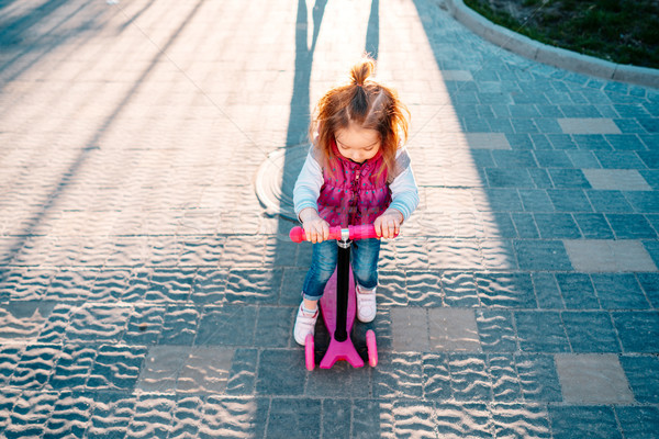 Little girl with blonde hair rides on scooter Stock photo © tekso
