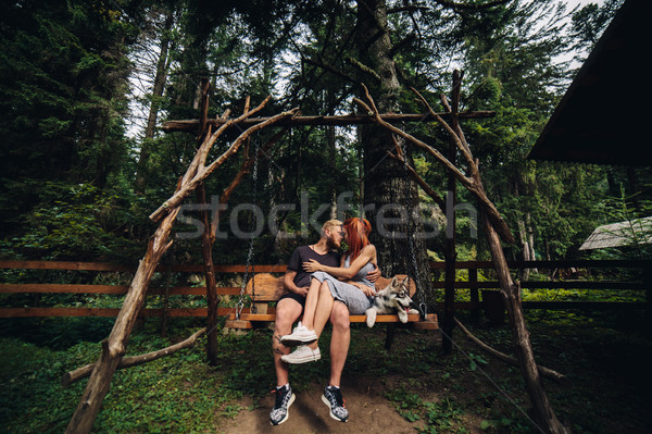beautiful couple together with dog on a swing Stock photo © tekso