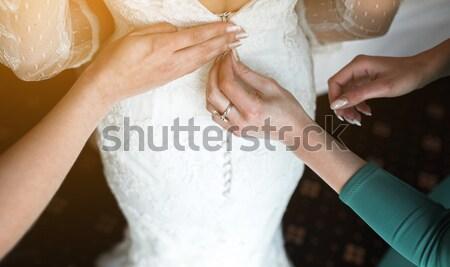 Bride putting on her dress Stock photo © tekso