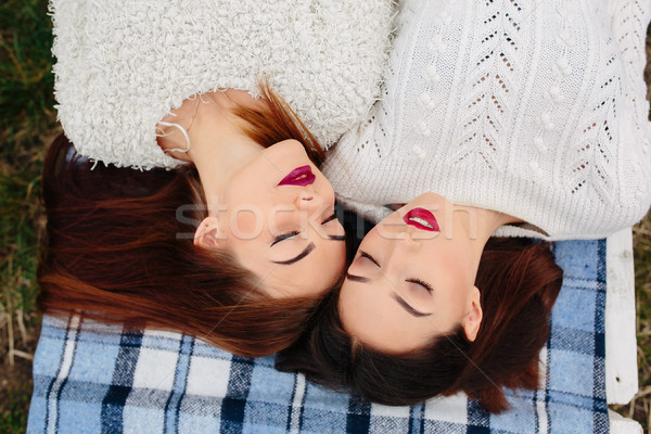 Two beautiful girls lie on the bench Stock photo © tekso