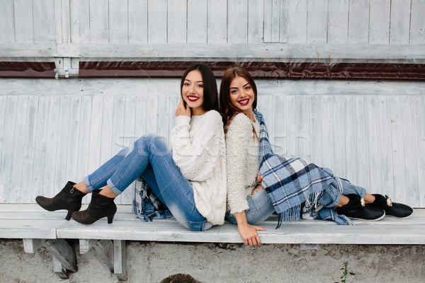 Iki kızlar oturmak bank park poz Stok fotoğraf © tekso