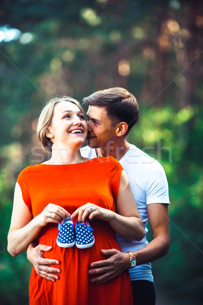 Pregnant wife and her husband holding baby shoes Stock photo © tekso