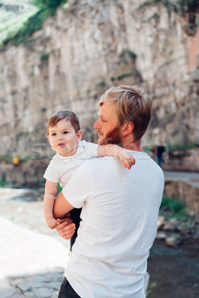 Dad and little son standing near a rock wall Stock photo © tekso