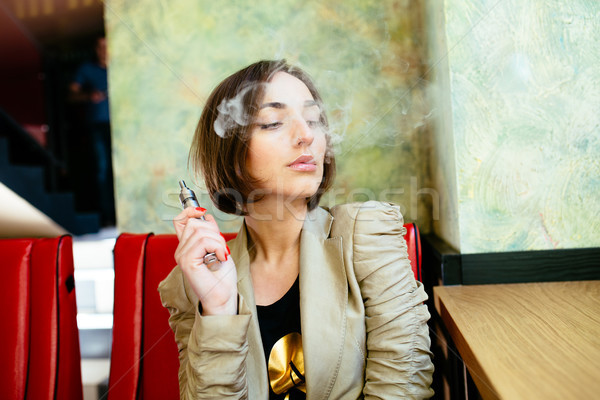 Fille électronique cigarette mystérieux jeune fille femme Photo stock © tekso