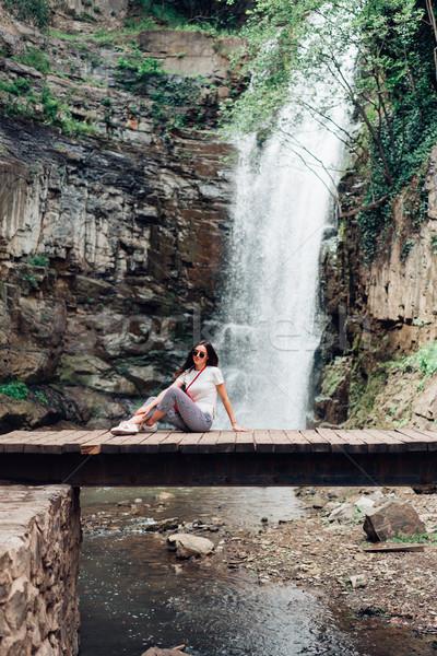 The girl sits on a bridge Stock photo © tekso