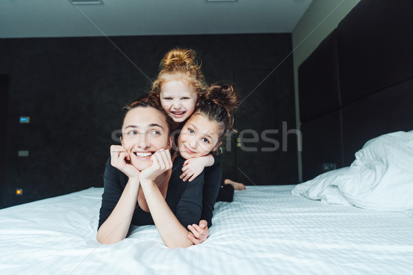 Mom and two daughters have fun on the bed Stock photo © tekso