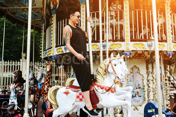 woman sitting at horse on a carousel Stock photo © tekso
