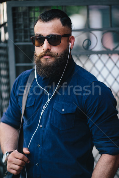 bearded man standing and listening to music Stock photo © tekso
