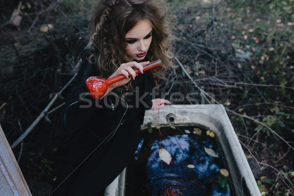 Stock photo: Vintage witch with elixir in hand