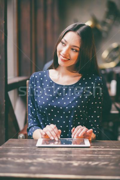 Gyönyörű lány dolgozik tabletta mosolyog nano telefon Stock fotó © tekso