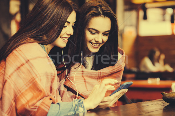 Stock photo: Two girl sitting listening to music