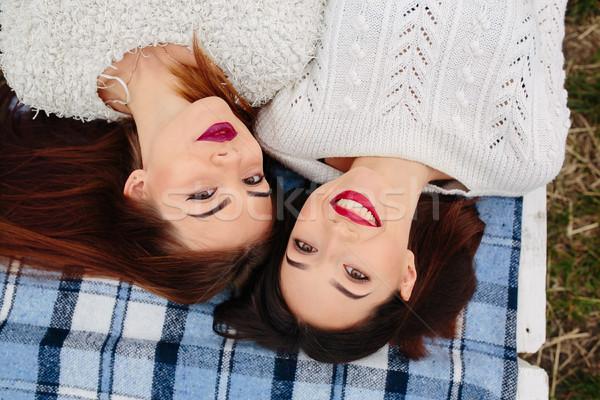 два красивой девочек лежать скамейке глядя Сток-фото © tekso