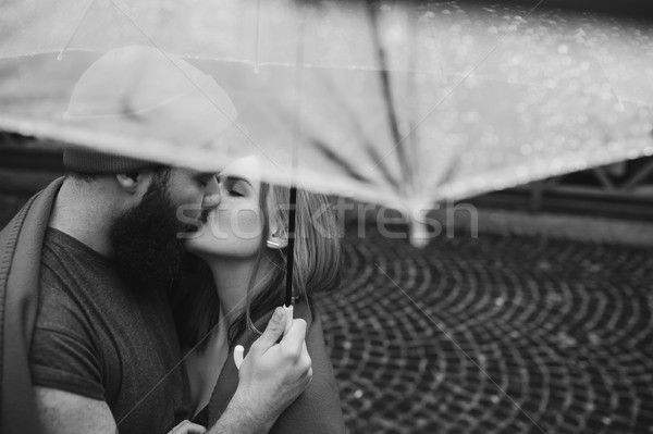 guy and the girl kissing under an umbrella Stock photo © tekso