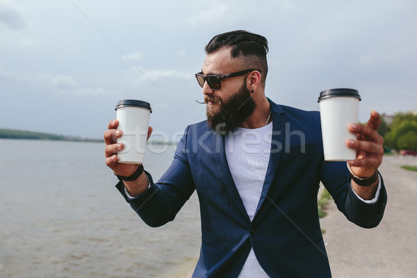 well-dressed man carries coffee Stock photo © tekso