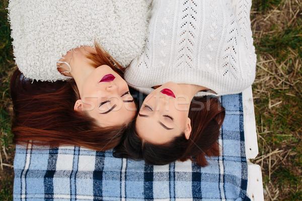 Dois belo meninas mentir banco olhando Foto stock © tekso