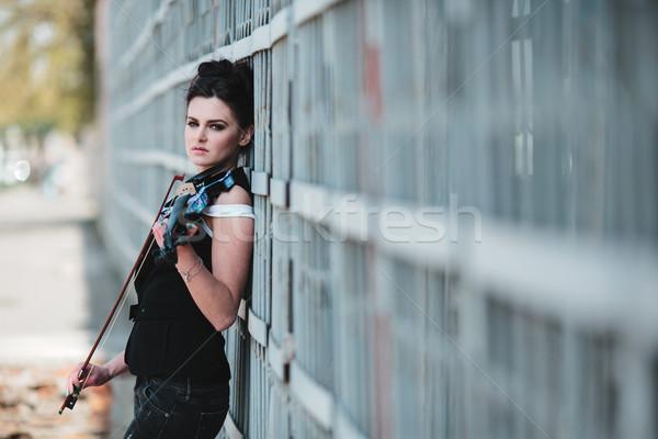 Dziewczyna stwarzające skrzypce strony ściany młodych Zdjęcia stock © tekso