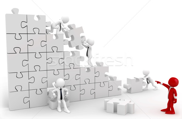 Director and employees working together to put the pieces of a puzzle Stock photo © texelart