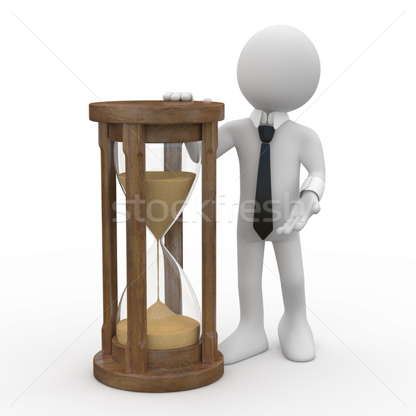 Stock photo: Man with tie and suit, leaning on an hourglass