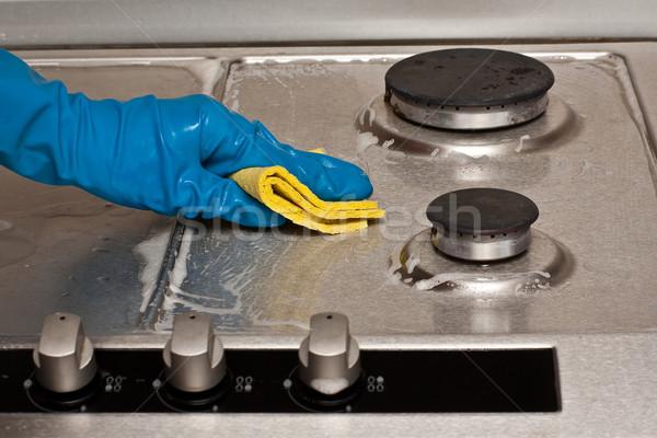 Trabalhos domésticos mão azul luva alto fogão Foto stock © timbrk