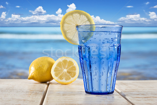 a Blue glass with sparkling water and lemon on a wooden deck overlooking a tropical beach Stock photo © tish1