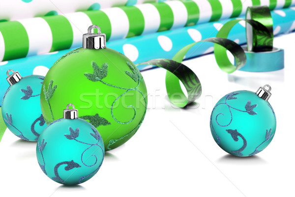 Rolls of gift wrapping paper and ribbon with blue and green christmas baubles Stock photo © tish1