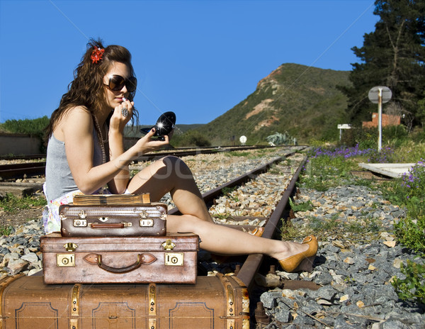 Young traveling woman with her suitcases on the railway tracks Stock photo © tish1