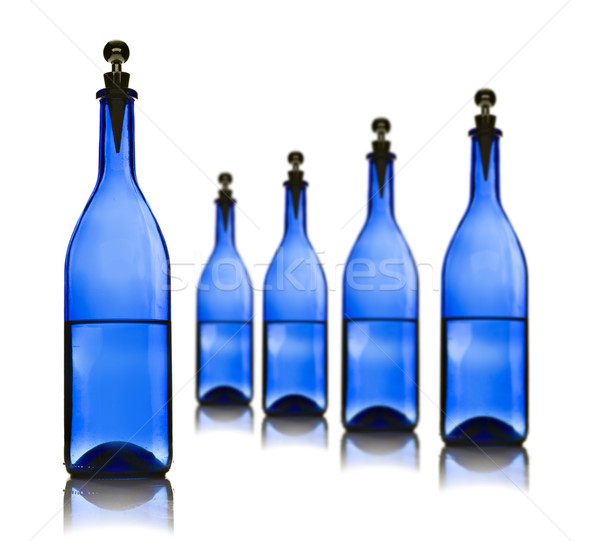 Five blue glass bottles with water on a white Stock photo © tish1