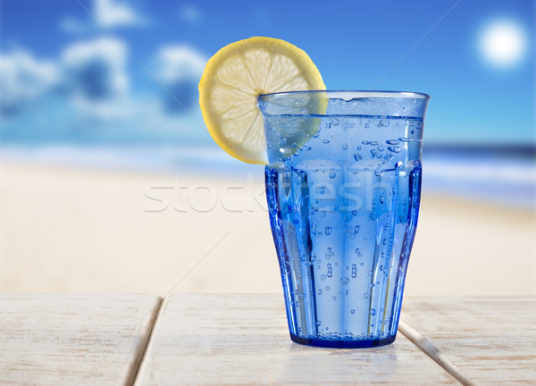 a Blue glass with sparkling water and lemon on a wooden deck overlooking a tropical beach - focus on Stock photo © tish1